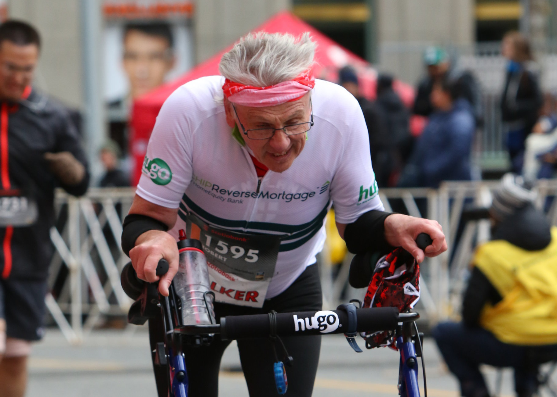 A photo of Robert Bob Hardy The Walker Runner, speed walking at the Toronto Marathon in October 2018 with his walker. Photo by Toronto Marathon, used on the website bobhardythewalkerrunner.com, designed and hosted by Evolvingmedia.com